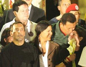 El presidente de Venezuela, Hugo Chávez, besa a la ex congresista colombiana Gloria Polanco de Lozada y a su hijo Sebastian Lozada Polanco.