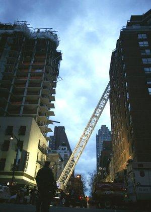 La grúa se partió en pedazos a medida que caía. Una parte chocó contra una torre de apartamentos y se estrelló en sus pisos superiores.