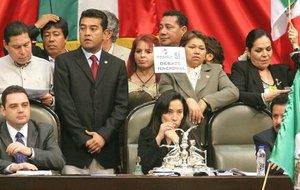 Decenas de diputados opositores cubrieron la tribuna de su cámara legislativa con una inmensa pancarta con la leyenda Clausurado y algunos establecieron un perímetro vistiendo cascos similares a los que usan los empleados de la paraestatal Petróleos Mexicanos (Pemex).