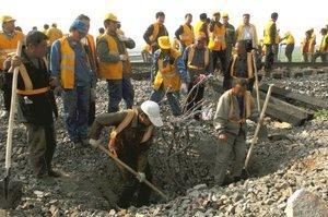 Varios trabajadores del ferrocarril reparan las vías en el lugar donde ocurrió el accidente.