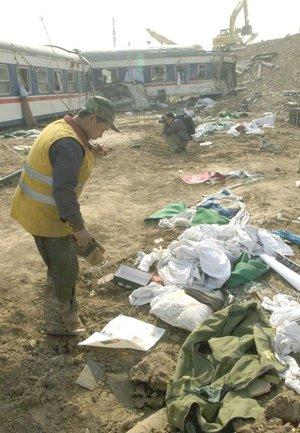 Un trabajador del ferrocarril observa las pertenencias de los viajeros en el lugar donde han descarrilado dos trenes de pasajeros cerca de la ciudad de Zibo, en la provincia de Shandong, al noreste de China.