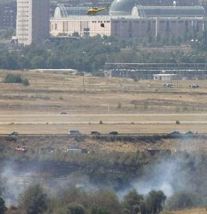 Humo en las proximidades del lugar en el que se ha estrellado el avión de la compañía Spanair que se salió  de la pista en el aeropuerto madrileño de Barajas mientras despegaba.