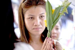 En playas de Tailandia, donde millares de pobladores y turistas murieron, parientes y amigos de las víctimas se congregaron en servicios religiosos, incluido uno en la bajo palmeras ante cientos de curiosos.