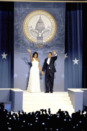 El presidente de Estados Unidos, Barack Obama, y su esposa, Michelle, saludan a su llegada al Baile de los Estados del Este, organizado con motivo de su investidura en el DC Armory de Washington.