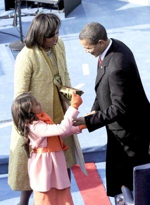 El presidente Barack Obama recibe la enhorabuena de su pequeña hija, Sasha, y su esposa Michelle, tras jurar el cargo.