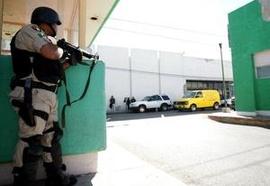 Un guardia del penal de Ciudad Juarez vigila el traslado a un hospital de reclusos heridos.