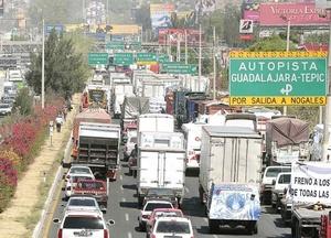 Severo caos vial en la carretera a Chapala, a la altura del Periférico, provoca el paro de transportistas afiliados a la CONATRAM.