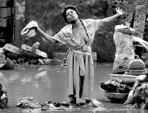 Mujer que intenta lavar su ropa en un río lleno de lodo en Goinaives.