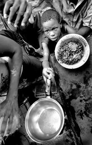 Clayson Menthor, 13 años, intenta obtener un plato de comida.