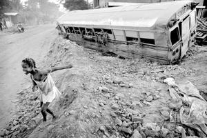 Una niña salta de la puerta de un bus escolar abandonado en Gonaives.