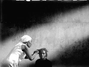 Silfika Sulme hace trenzas en el cabello de una amiga en Goinaves.
