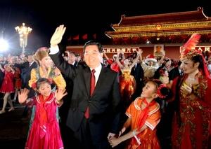 El presidente Hu Jintao, que vestía un saco al estilo Mao en vez de un traje de gala occidental, iba a bordo de una limosina con una bandera roja para pasar revista a los miles de soldados.