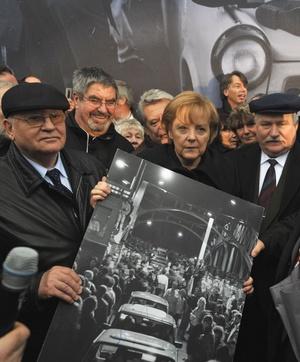 La canciller alemana Angela Merkel y los ex presidentes soviético Mijail Gorbachov y polaco Lech Walesa, sostienen una fotografía de personas cruzando la frontera luego de la caída del Muro de Berlín, al inicio de la conmemoración del suceso.