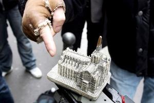 Un hombre señala una réplica del Duomo de Milán, normalmente vendido como 'souvenir' en la ciudad, objeto que un hombre arrojó al primer ministro italiano, Silvio Berlusconi.