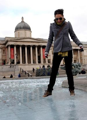 Una turista camina por una de las fuentes heladas de la plaza de Trafalgar en Londres, Inglaterra.