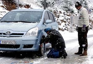 Conductores griegos colocan las cadenas en el coche que conducían por una carretera nacional en las inmediaciones de Nevrokopi, al norte del país, donde ha caído una intensa nevada.