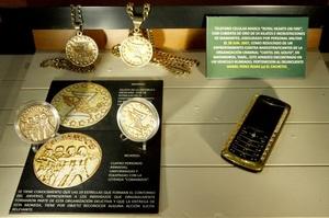 Detalle de joyería adquirida por narcotraficantes donde se observan monedas, cadenas y un celular de oro con incrustaciones de piedras preciosas.
