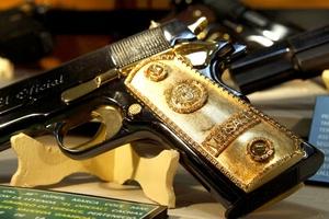 Detalle de una pistola calibre 0.38 Súper con cachas doradas y el símbolo de Versace que perteneció al narcotraficante Héctor Manuel Sauceda Gamboa, operador del cártel de Cárdenas Guillen.