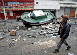Un niño observa un bote  destruido por el  terremoto de 8,8 grados que sacudió en la madrugada del pasado sábado el centro y sur del país de Chile.