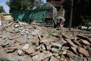 Un hombre busca entre los escombros en Santiago Chile tras terremoto.