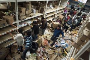 Una multitud saquea un supermercado  a raíz de la falta de alimentos provocada por el terremoto.