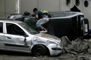 Un joven saquea un carro destruido por un terremoto.