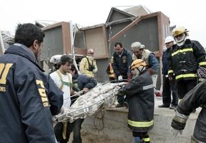 Rescatistas chilenos trasladan el cuerpo de un hombre que fue encontrado en los escombros.