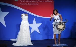 La primera dama de EEUU, Michelle Obama, ofrece un discurso durante la ceremonia en la que ha donado el vestido color marfil de un solo hombro que vistió durante los bailes inaugurales de la presidencia de su marido, Barack Obama.