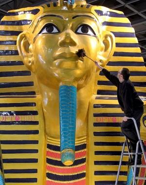 Un empleado limpia una enorme máscara faraónica que parte de un stand en la Bolsa Internacional de Turismo de Berlín (ITB) en Berlín, Alemania la feria abre hoy sus puertas con previsiones esperanzadoras que apuntan a que lo peor de la crisis económica y financiera mundial y sus efectos sobre el sector han pasado.