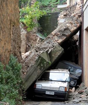 Imagen de un muro que se desprendió sobre dos vehículos tras las fuertes lluvias ocurridas en Cosenza, en la región sureña de Calabria, Italia.