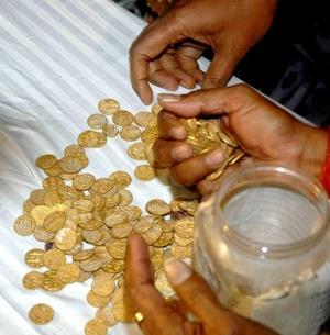 Funcionarios del departamento de arqueología del distrito Burhanpur de la región de Madhya Pradesh, (India), muestran las 482 monedas de oro descubiertas durante unas excavaciones.