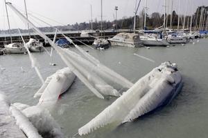 Unos veleros se hunden por el peso del hielo en el puerto del lago Ginebra en Versoix, cerca de Ginebra, Suiza.