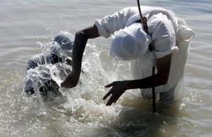 Un sacerdote mandaeano (dcha) bautiza a un fiel en el río Tigris durante la tercera jornada del festival Benja en Bagdad, Irak. Benja es una festividad religiosa que celebran los miembros de la minoría mandaeana celebran durante cinco días.
