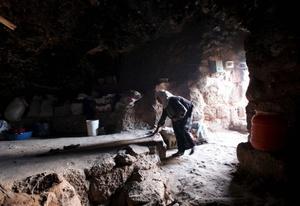 Una mujer palestina arregla el interior de la cueva en la que vive con su familia en la localidad cisjordana de Yatta.