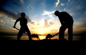 Dos hombres musulmanes cachemiríes trabajan en las orillas del lago Dal en Srinagar, la capital de verano de la zona de Cachemira administrada por la India, al atardecer.