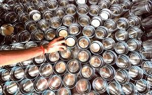 Un empleado coloca utensilios de cocina en la unidad de acero inoxidable de una fábrica local de artículos de cocina en Mumbai, India.