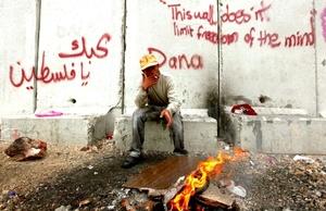 Un palestino se calienta junto a una hoguera prendida frente al polémico muro de separación, cerca del punto fronterizo de Kalandia.