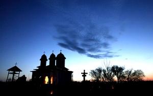 La silueta de una capilla ortodoxa se recorta en el horizonte durante la celebración de la misa de Jueves Santo por los difuntos en el cementerio de la localidad de Naipu en el sur de Rumanía.