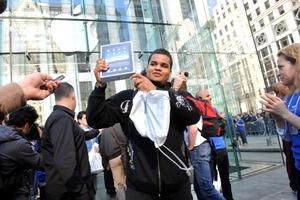 Uno de los primeros compradores sostiene la tableta de Apple a la salida de una tienda de la Quinta Avenida de Nueva York.
