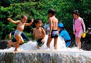 Un grupo de niños juega con el agua en una fuente en el centro de Tokio, Japón.