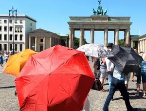 Turistas se protegen del sol durante un día en el que el termómetro ha alcanzado temperaturas de 36 grados.