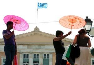 Personas se protegen del sol con sombrillas, en pleno centro de Atenas, Grecia, donde el termómetro ha alcanzado temperaturas de 40º grados.