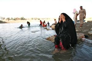 Una mujer iraquí vierte el agua sobre su cuerpo para refrescarse por el río Tigris en Bagdad, Irak. La Administración General de Supervisión Meteorológica y Sísmica informó que Las temperaturas alcanzarán los 50 grados centígrados en Bagdad.