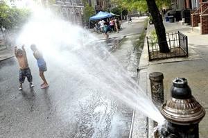 Niños juegan con el agua que escapa de un hidrante para refrescar el ambiente en el cuarto día de temperaturas record en la 101 Street en Harlem, Nueva York , EE.UU.