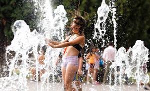 Una niña disfruta refrescándose en una fuente en Podolsk a unos 16 km de Moscú en Rusia. Una ola de calor está cubriendo Rusia donde se están alcanzando temperaturas récord de 37 grados.