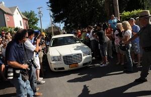 Medios y curiosos rodean un vehículo lleno de invitados en Rhinebeck, Nueva York, Estados Unidos, donde celebra la boda de Chelsea Clinton, hija del ex presidente estadounidense William Clinton, con el banquero Marc Mazvinsky en la mansión Astor Courts de Rhinebeck.