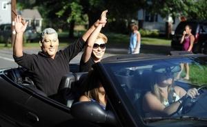 Varias personas, usando máscaras de Bill y Hillary Clinton, viajan en un vehículo convertible, en la vía cercana al sitio donde se celebra la boda de Chelsea Clinton, hija del ex presidente estadounidense William Clinton, con el banquero Marc Mazvinsky en la mansión Astor Courts de Rhinebeck, Nueva York.
