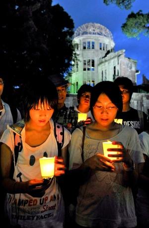Un grupo de personas porta velas durante una ceremonia de recuerdo de las víctimas de la bomba atómica de Hiroshima.