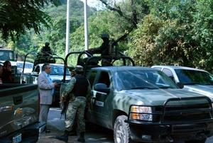 El procurador de Justicia de NL, Alejandro Garza y Garza, platicó con militares en el lugar donde fue localizado el cadaver del alcalde de Santiago.