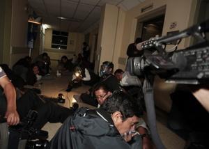 Miembros de la prensa nacional e internacional se protegen en el piso del fuego cruzado mientras militares sacan al presidente de Ecuador.